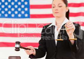 Close up of a young judge knocking a gavel and holding scales of
