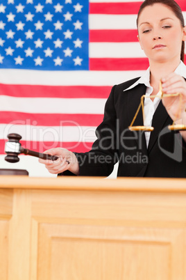 Portrait of a cute judge knocking a gavel and holding scales of