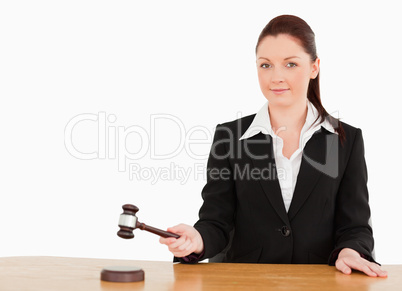 Young judge knocking a gavel smiling at the camera