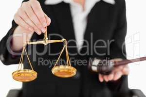 Young woman holding scales of justice and a gavel with the camer