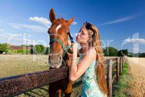horse and blond girl in paddock on summers
