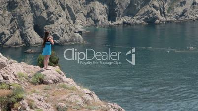 young woman standing on the edge of  cliff