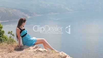 woman sitting on  edge of cliff by the sea
