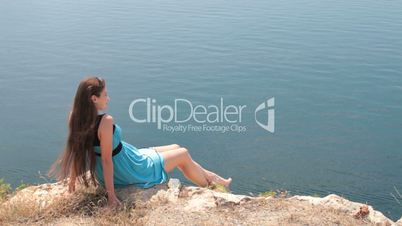 young woman resting on edge of  cliff by the sea