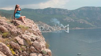 Woman sitting on the edge of a cliff