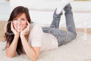Charming brunette female posing while lying on a carpet
