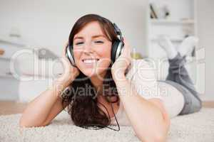 Glad brunette woman using headphones while lying on a carpet