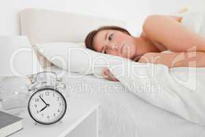 Lovely brunette woman awaking with a clock while lying