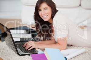 Young charming woman relaxing with her laptop while lying on a c