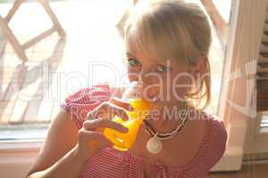 young blond woman drinks juice out of a glass