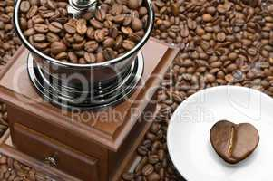 Old coffee grinder and heart on a saucer