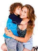 Young kid kissing his mom and looking at camera