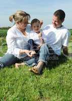Junge Eltern mit Kleinkind im Sommer auf der Wiese