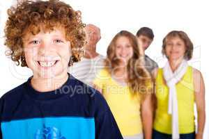 Adorable young kid in focus with family in the background