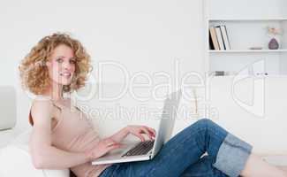 Attractive blonde woman relaxing with her laptop while sitting o