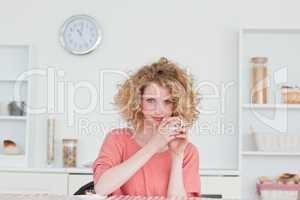 Good looking blonde woman drinking a cup of coffee while sitting