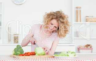 Charming blonde woman cooking some vegetables in the kitchen