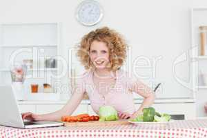 Beautiful blonde woman relaxing with her laptop while cooking so