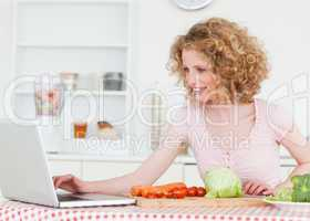 Attractive blonde woman relaxing with her laptop while cooking s