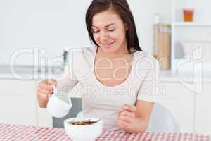 Brunette pouring milk in her cereal