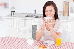 Charming brunette having her breakfast