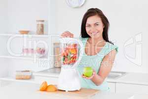 Happy woman with a blender and an apple
