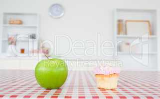 An apple and a cupcake on a tablecloth