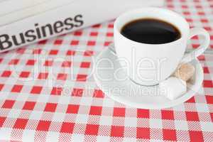 A cup of coffee and a newspaper on a tablecloth