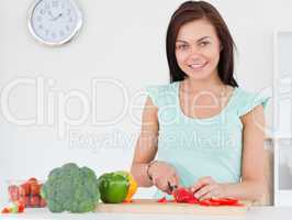 Woman slicing a pepper while looking at the camera