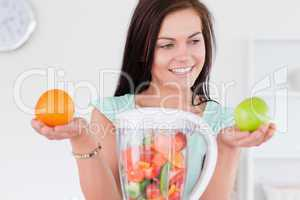 Charming woman with a blender and fruits