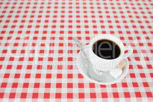 A cup of coffe on a tablecloth