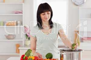 Attractive brunette woman cooking vegetables