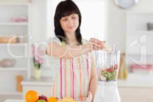 Pretty brunette woman putting vegetables in a mixer while standi