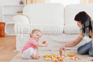 Cute woman playing with her baby in while sitting on a carpet