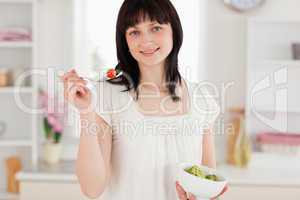 Attractive brunette female eating a cherry tomato while holding