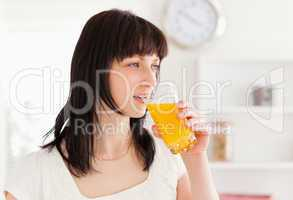 Good looking brunette drinking a glass of orange juice while sta