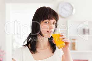 Pretty brunette drinking a glass of orange juice while standing