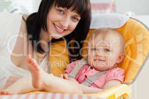 Good looking brunette woman posing with her baby while sitting