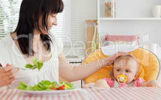 Good looking brunette woman eating a salad next to her baby whil