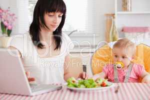 Gorgeous brunette woman eating a salad next to her baby while re