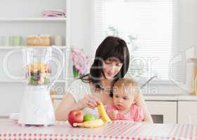 Cute brunette woman showing a banana to her baby while sitting