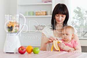 Gorgeous brunette woman pealing a banana while holding her baby
