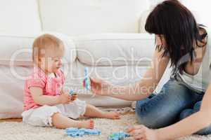 Beautiful woman and her baby playing with puzzle pieces while si