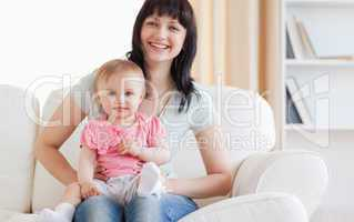 Pretty woman holding her baby in her arms while sitting on a sof