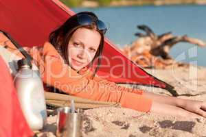 Camping happy woman in tent by campfire