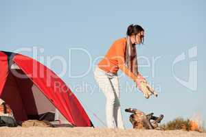 Camping happy woman making campfire on beach