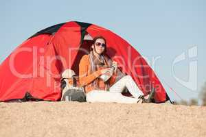 Camping happy woman sitting front of tent