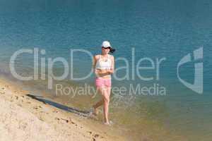 Summer sport fit woman jogging along seashore