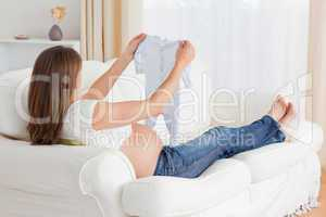 Charming pregnant woman looking at a baby grow while lying on a