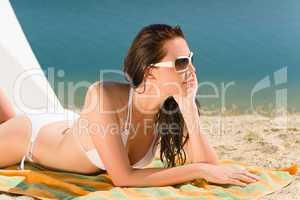 Summer beach young woman sunbathing in bikini